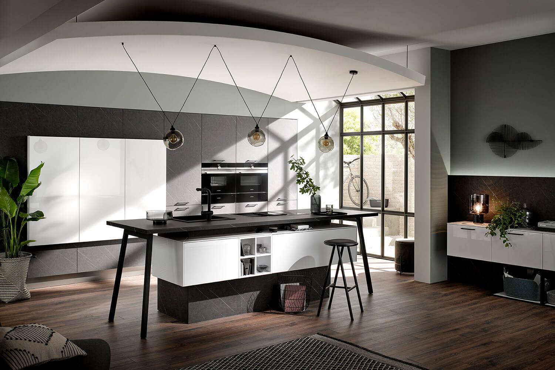 Einbauküche mit moderner Kücheninsel mit Thekenlösung in dunkler Marmor-Optik mit Polarweiß kombiniert