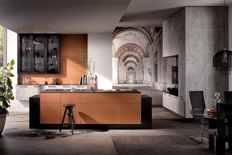 moderne grifflose Küche mit Küchenblock in Kupfer mit Hochschrank mit grauer Marmor-Optik